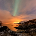 The beaches near Tromso under an Aurora Borealis, with the light pollution of the city.