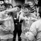 "A group of friends laughing loudly after carriing a ""Mikoshi"" (Shinto shrine) in a sintoism celebration."